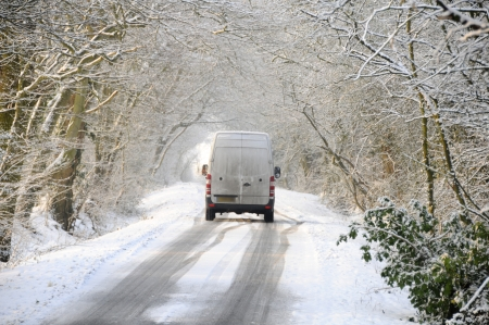 inclement: Van driving on winter snow covered country lane through woodland trees