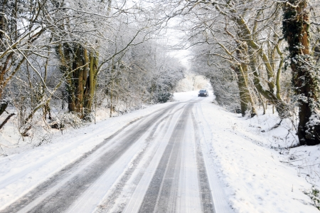 inclement weather: Distant car driving on winter snow covered country lane through woodland trees