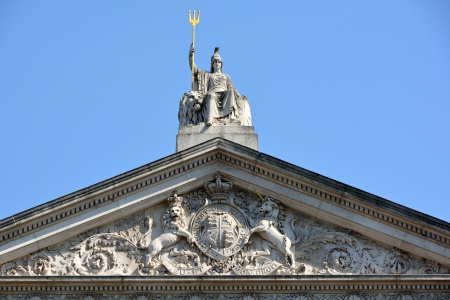 britannia: Britannia statue with Trident, and Coat of arms at roof level on Somerset House London Stock Photo