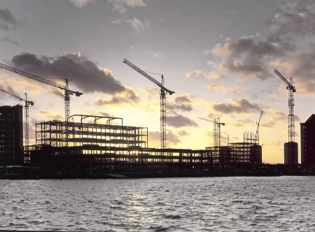 new site: Setting sun behind waterside steel framed building site for new office development project