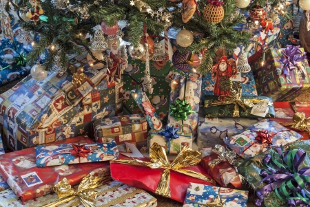 Gift wrapped presents below a fully decorated Christmas tree  photo