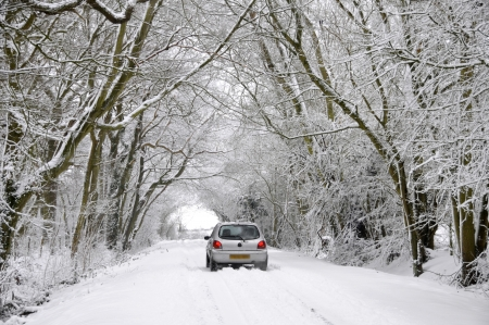 inclement: Driving through a snow covered country lane in a winter wonderland