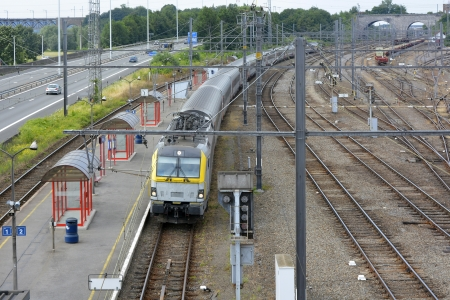 railway engine: Vise railway station platform and train Belgium with motorway alongside