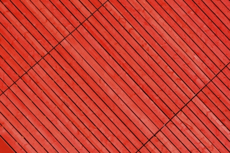 diagonally: Red stained timber slats viewed diagonally to create abstract pattern background
