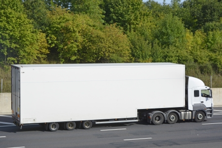 by the side: Clean unmarked white articulated truck and trailer on motorway Stock Photo