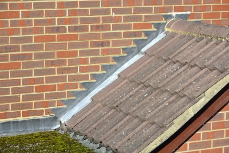 flashing: Stepped lead flashing at sloping roof tile abutment to brick wall and flat roof