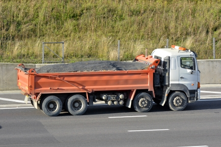 haulage: Tipper Lorry with dust sheet covering bulk materials driving along motorway