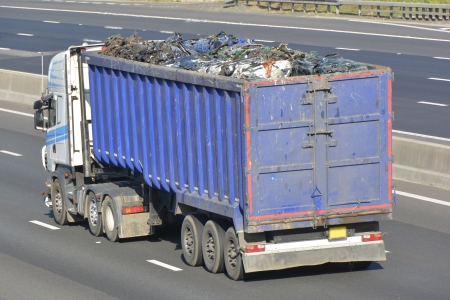 haulage: Articulated truck and trailer loaded with scrap metal driving along motorway