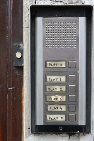 intercom: Entry intercom push buttons to numbered flats beside door bell Stock Photo