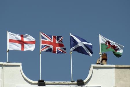 welsh flag: Unione bandiera modo sbagliato con inglesi gallesi bandiere scozzesi volare dalla cima del palazzo dell'hotel