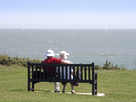headwear: Senior citizens couple relaxing on cliff top bench seat with view out to sea and sail boats