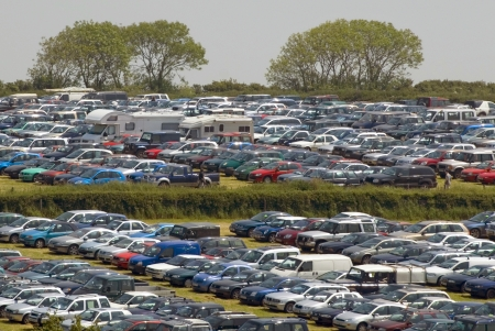 Visitors overflow car parking on farmland adjacent to summer rural county agricultural showground event Stock Photo