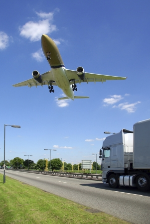 Low flying aircraft approaching airport passing over truck on dual carriageway road photo