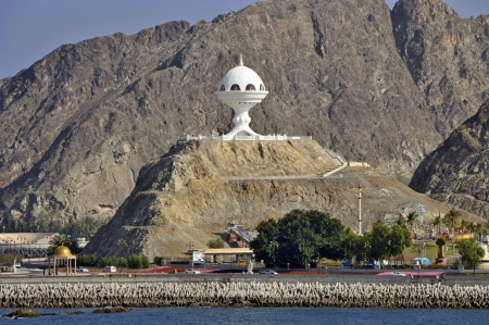 muscat: Muscat Oman white incense burner on hillside with waterfront protected with Dolos concrete blocks