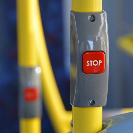 command button: Close up of a stop button fitted to grab rail on a passenger bus