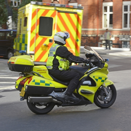 ambulance: Motorcycle paramedic and ambulance attending at scene of an incident in a town centre Stock Photo