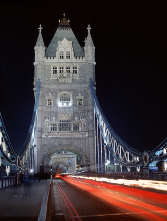Night-time traffic crossing floodlit Tower Bridge in London photo