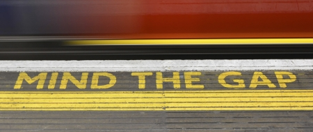 Mind the Gap warning and blurred train on London railway photo