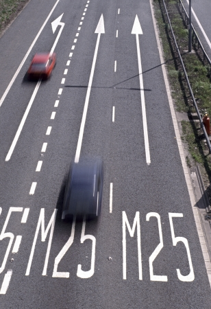 motorway: M25 London orbital motorway long arrows   signs painted on tarmac with motion blur cars Stock Photo