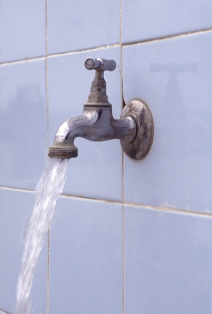 splashback: Running water flowing from outdoor tap with blue tiled splashback