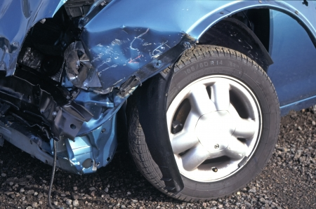 buckled: Smashed front corner of blue car after being involved in a road traffic accident Stock Photo