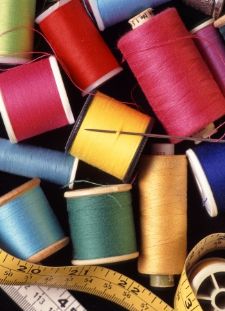 muddle: Sewing threads and cotton reels in close up of needlecraft basket  Stock Photo