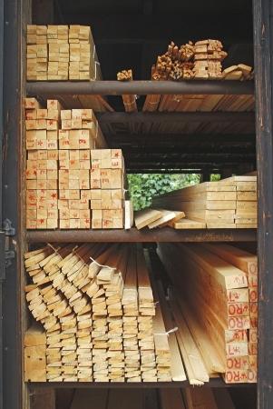 materia prima: Patio de la madera con la madera cepillada dispuesto en bastidores esperando selección y compra