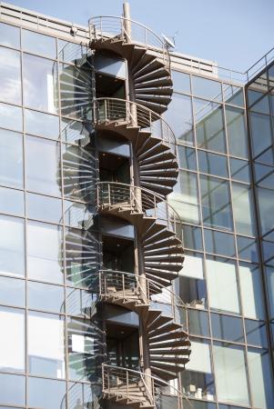 salidas de emergencia: Escapar escalera de incendios espiral en la pared externa del edificio de oficinas con reflejos en los muros cortina