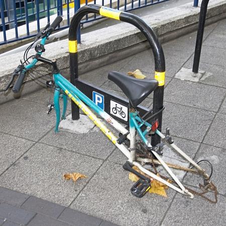cicla: Restos de una bicicleta con sólo bastidor principal con candado para plaza de aparcamiento de moto oficial