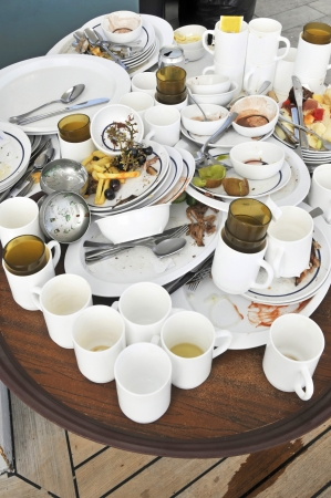 leftover: Dirty crockery and left over food on table after party