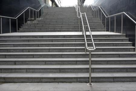 down the stairs: Amplio tramo largo de la escalera exterior con pasamanos de acero inoxidable Foto de archivo