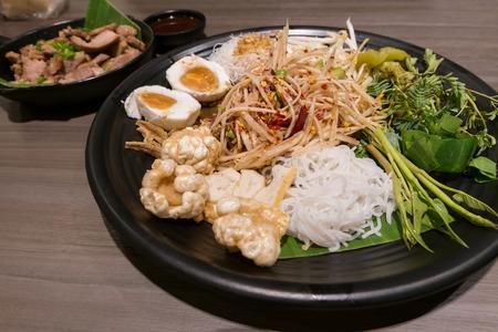 Som Tum or Thai style papaya salad in tray at restaurant