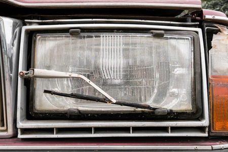 wiper: Close up a headlight with a wiper detail on old car