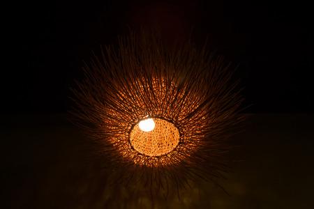 electric fixture: Decorative wicker lamp in dark room. Asian decor Stock Photo