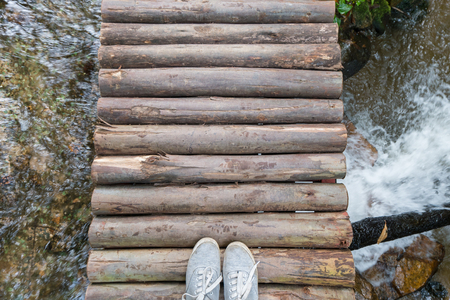 shoelace: Top view gray sneakers on wooden bridge over river, Hipster style