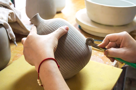 Potters hands make a decorative pattern on vase