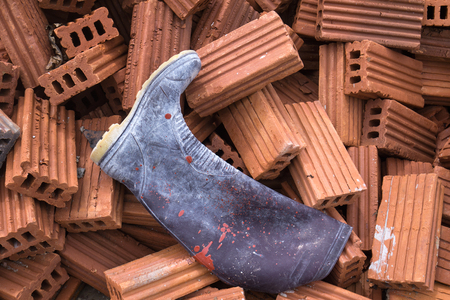 dirty rubber boot on pile of orange bricks for construction