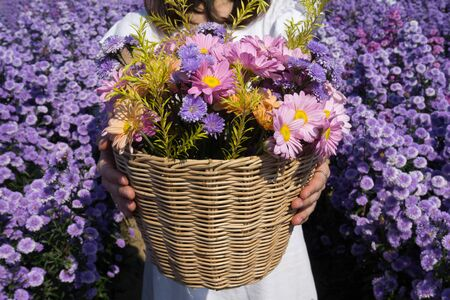 Woman holding basket with beautiful flowers in the Margaret garden