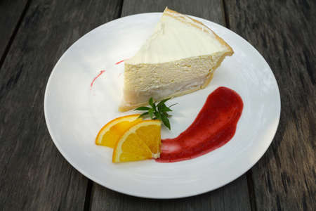 coconut cake with orange and strawberry sauce on white plate Фото со стока
