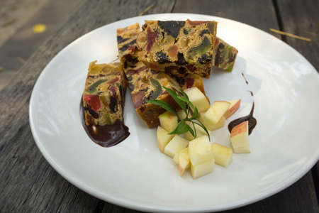 delicious sliced fruit cake with mixed fruit on wooden table