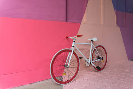 Bicycle with colorful (purple, blue pink and beige) wall as background