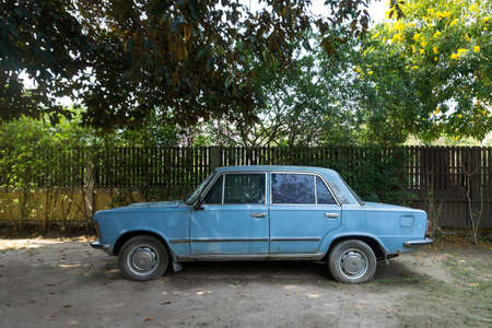 The old, abandoned blue car in a garden