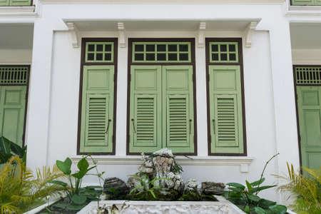 vintage green wooden shutter window on white building, Thailand