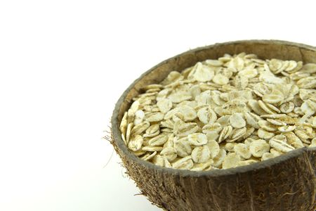 Wheat flakes in a coconut shell bowl isolated on white background photo
