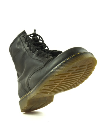 hiking boot:   Black leather heavy shoe in stomping action