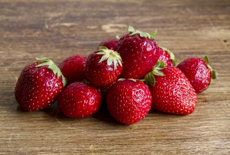 Fresh and ripe strawberries on a wooden background photo