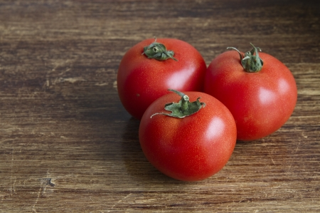 Three tomatoes with a wooden background Stock Photo - 13756184
