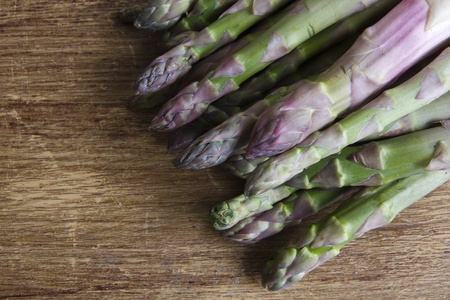 Raw and fresh asparagus on a wooden background