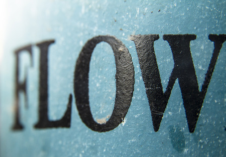 Word flow painted on a aged blue tin surface