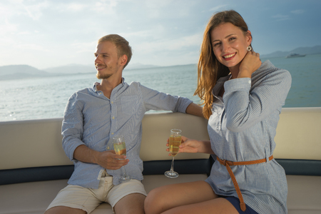 Romantic vacation. Beautiful couple drinking sparkling wine on the board of yacht